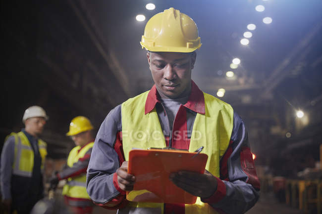 Steelworker with clipboard working in steel mill — Stock Photo