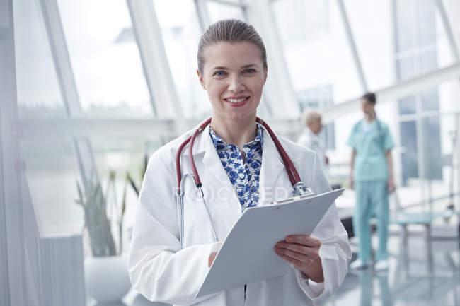 Retrato sorrindo, médico feminino confiante com área de transferência no hospital — Fotografia de Stock