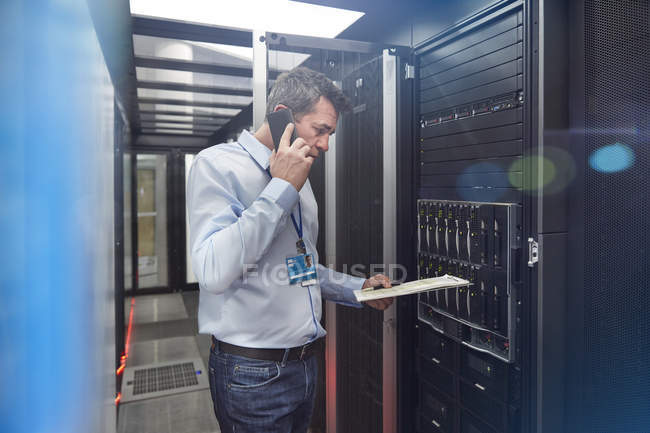 Male IT technician with clipboard talking on cell phone at panel in server room — Stock Photo