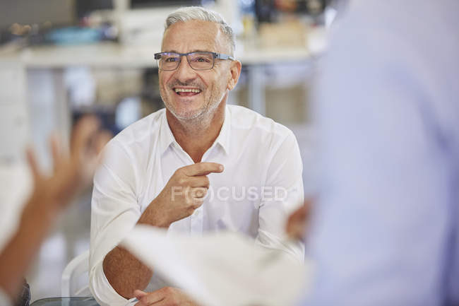 Smiling businessman in meeting at modern office — Stock Photo