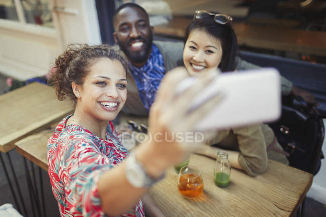 Smiling young friends taking selfie with camera phone at sidewalk cafe — Stockfoto