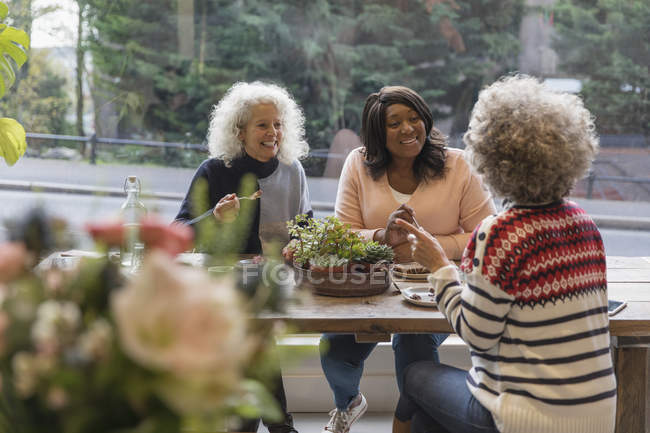 Women friends talking and eating lunch at cafe — Stock Photo