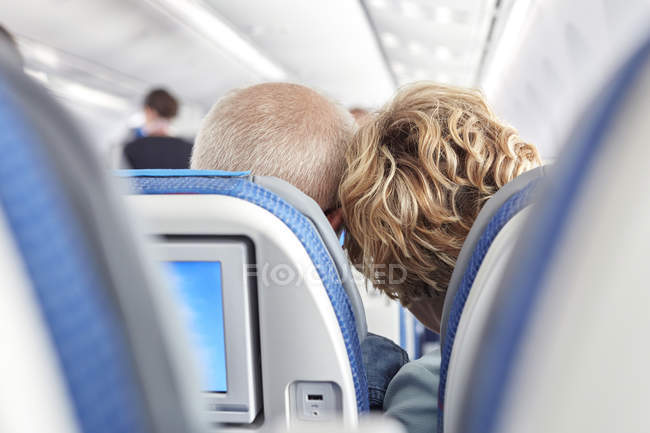 Rear view affectionate mature couple leaning on airplane — Stock Photo