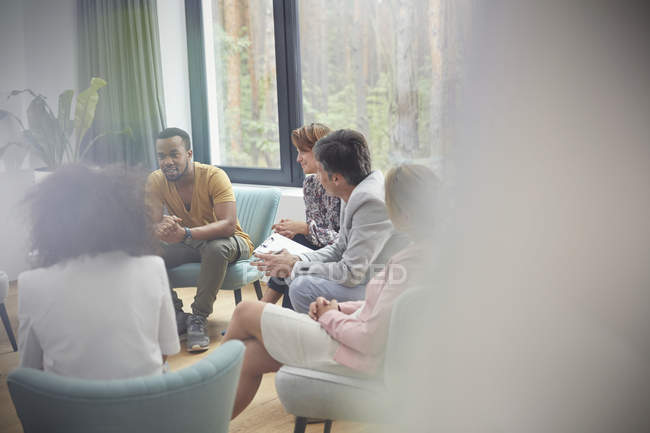 People listening to man in group therapy session — Stock Photo