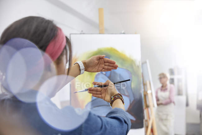 Female artist gesturing, framing painting on easel in art class studio — Stock Photo