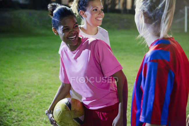 Playful, laughing young female soccer plays on field at night — Stock Photo