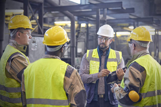 Supervisor talking with steelworkers in steel mill — Stock Photo