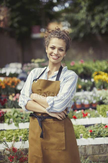 Улыбающаяся, уверенная в себе цветочница, работающая в цветочном магазине — стоковое фото