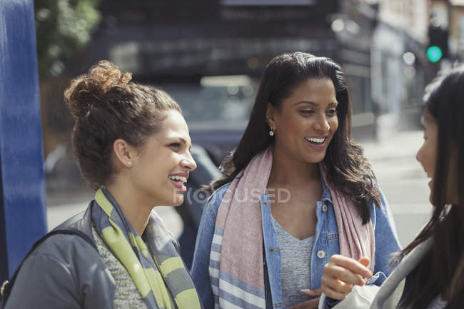 Smiling female friends talking on urban street — Stock Photo