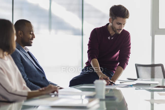 Businessman explaining paperwork in conference room meeting — Stock Photo