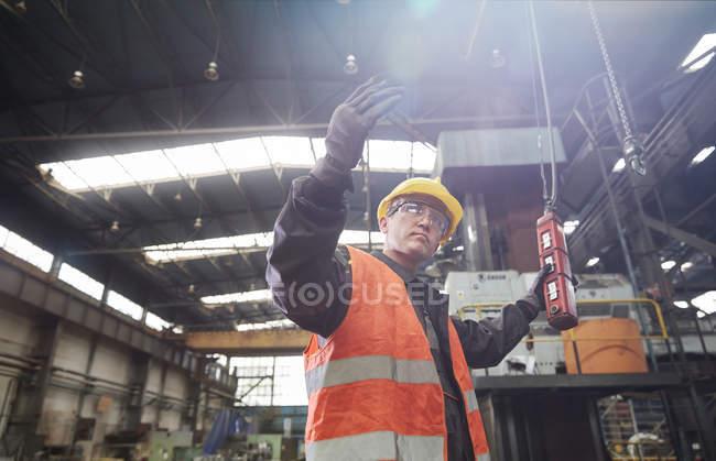 Macchine operaie maschili al pannello di controllo, gesticolando — Foto stock