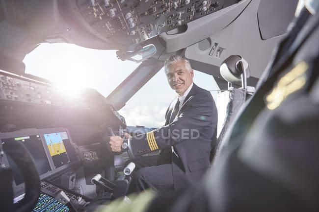 Os pilotos falando no cockpit do avião a sorrir — Fotografia de Stock