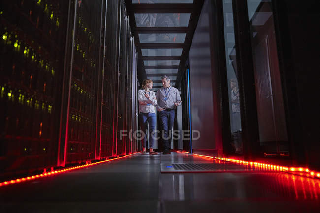 IT technicians talking and walking in dark server room — Stock Photo