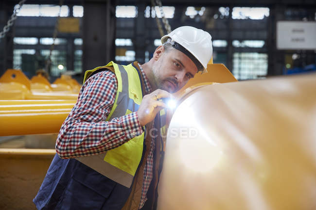 Focused male engineer with flashlight examining equipment in factory — Stock Photo