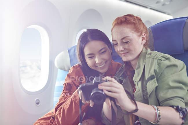 Sorridenti giovani amiche che guardano le foto sulla macchina fotografica digitale in aereo — Foto stock