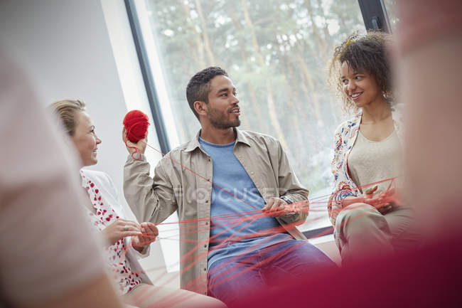Group therapy session doing team building exercise with yarn — Stock Photo