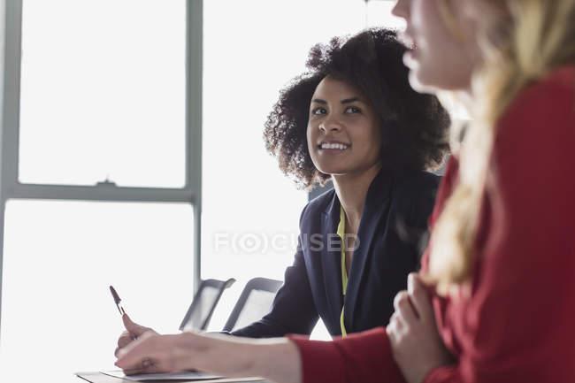 Mulher de negócios sorridente ouvindo na reunião da sala de conferências — Fotografia de Stock