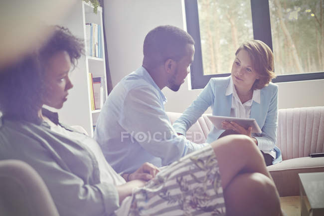 Female therapist with digital tablet comforting man in couples therapy session — Stock Photo