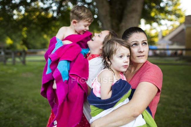 Lesbische Mütter halten nasse Kinder im Sommergarten in ein Handtuch gewickelt — Stockfoto