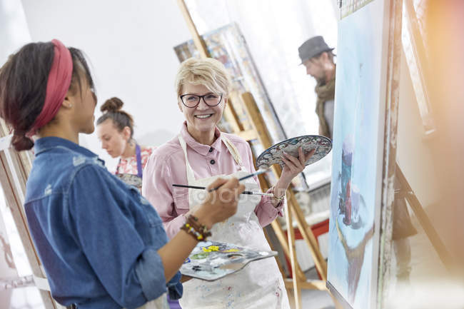 Smiling female artists with paintbrushes and palettes painting in art class studio — Stock Photo