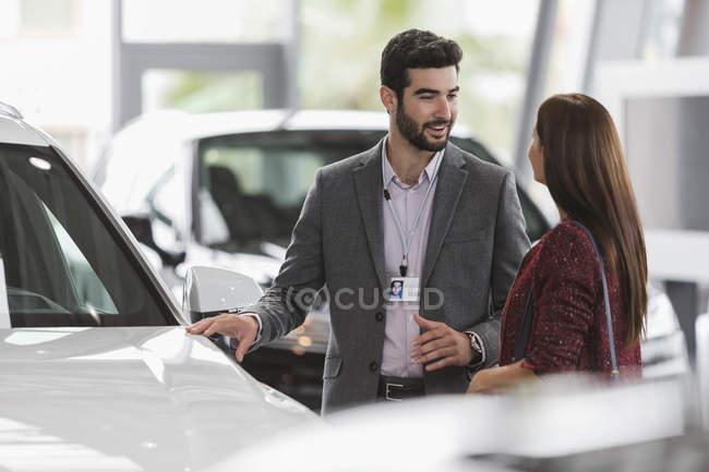 Продавец автомобилей показывает новую машину клиентке в салоне автосалона — стоковое фото