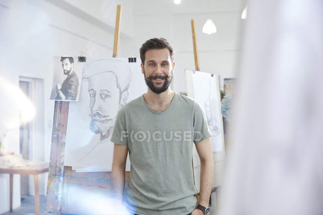 Retrato sonriente, seguro de artista masculino de dibujo en el estudio de la clase de arte - foto de stock