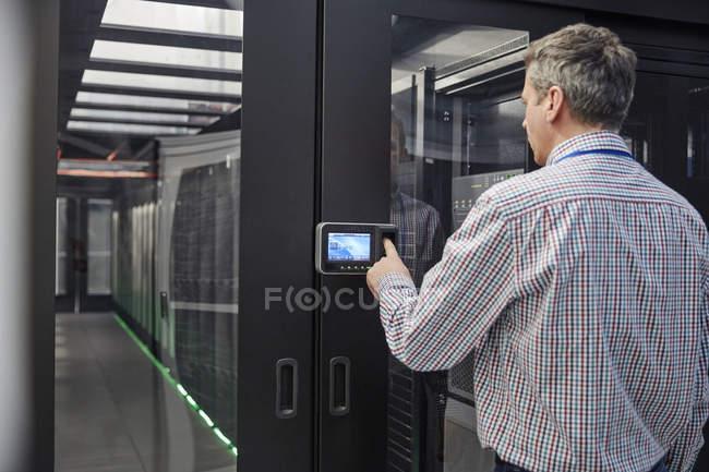 Male IT technician inputting security code at server room access door — Stock Photo