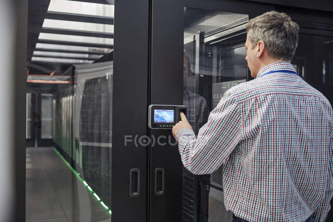 Male IT technician inputting security code at server room access door — Stock Photo