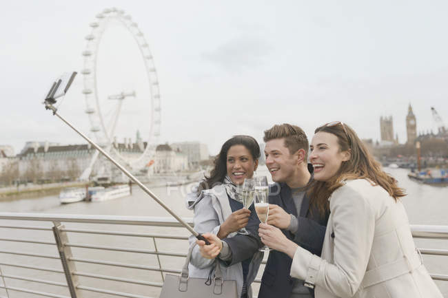 Smiling friend tourists celebrating, toasting champagne and taking selfie with selfie stick near Millennium Wheel, London, UK — Stock Photo
