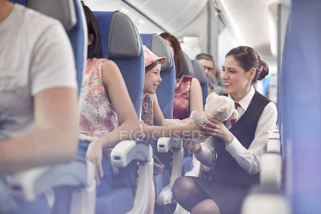 Niña con oso de peluche a mujer auxiliar de vuelo en avión - foto de stock