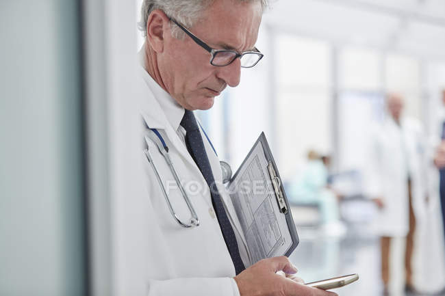 Male doctor with clipboard texting with smart phone in hospital — Stock Photo