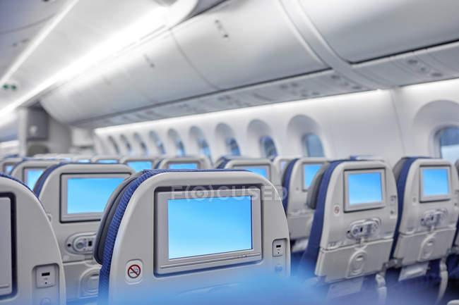 Unterhaltungsbildschirme auf Sitzen im Flugzeug — Stockfoto