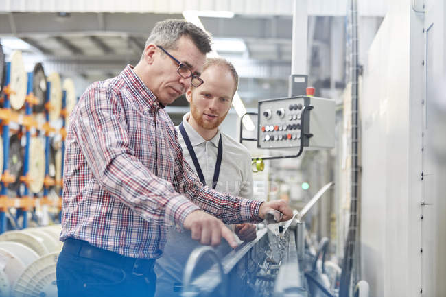 Male supervisor and worker examining machinery in fiber optics factory — Stock Photo