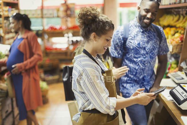 Caissier femelle avec calculatrice aidant les clients masculins en épicerie — Photo de stock
