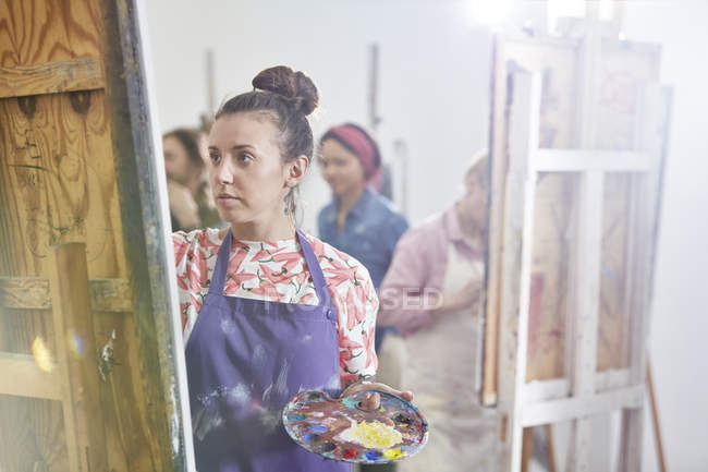 Focused female artist with palette painting at easel in art class studio — Stock Photo