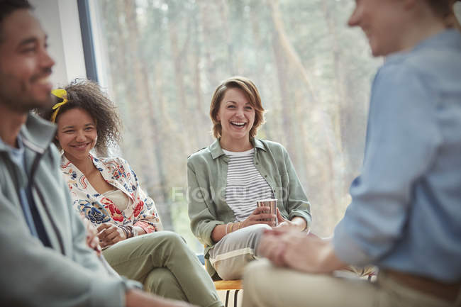 People smiling and laughing in group therapy session — Stock Photo