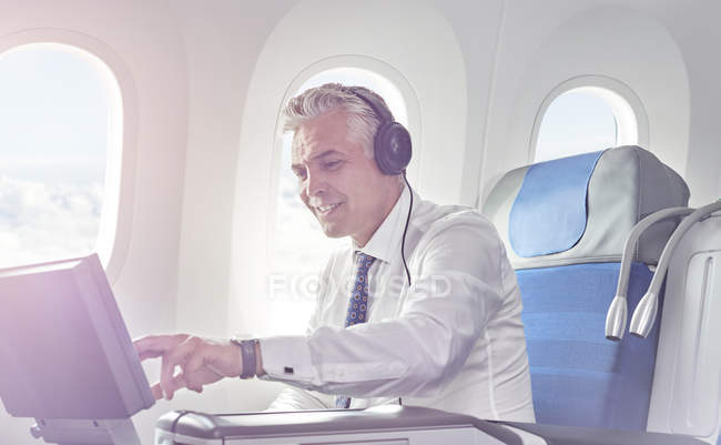 Businessman with headphones watching movie on airplane — Stock Photo