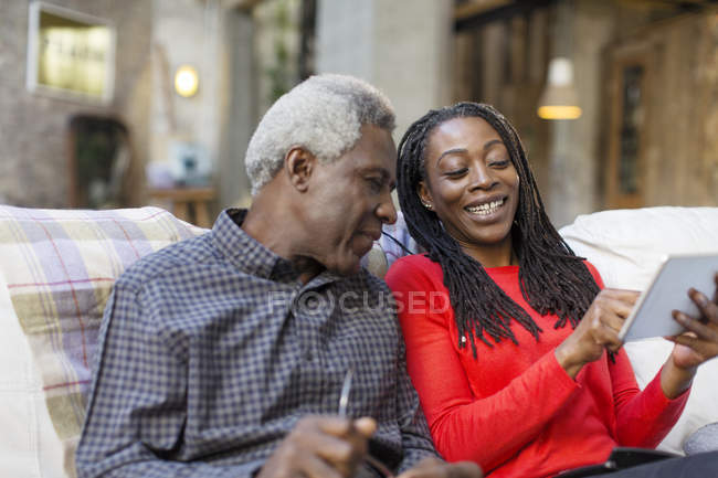 Adult daughter showing senior father how to use digital tablet — Stock Photo