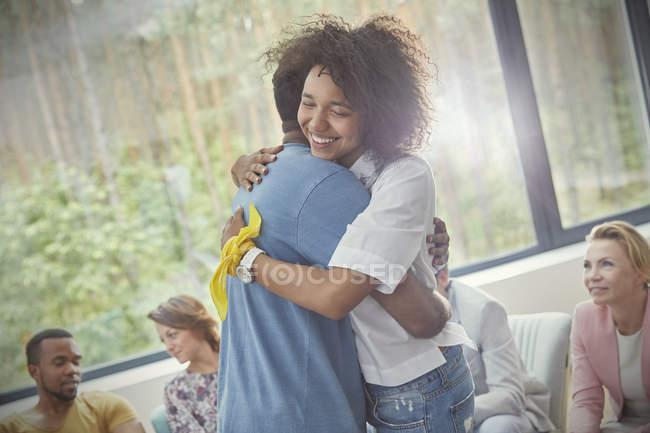 Улыбающаяся женщина обнимает мужчину на сеансе групповой терапии — стоковое фото