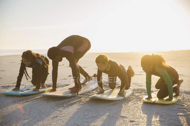 Father surfer teaching children surfing on surfboard on sunny summer beach — Stock Photo