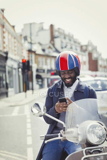 Jeune homme d'affaires souriant en casque sur scooter à moteur, textos avec téléphone portable dans la rue urbaine — Photo de stock