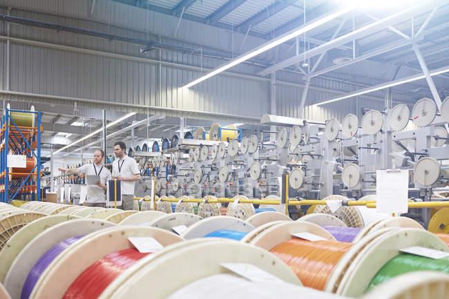 Мужской руководитель и работник проверяет инвентарь за многоцветными катушками на заводе волоконной оптики — стоковое фото