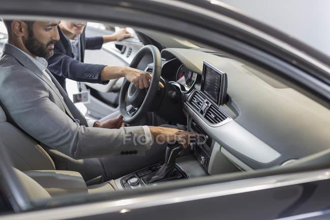 Автомобіль Продавщиця вказуючи, пояснивши новий автомобіль для чоловічого клієнтів у водія? s сидіння — стокове фото