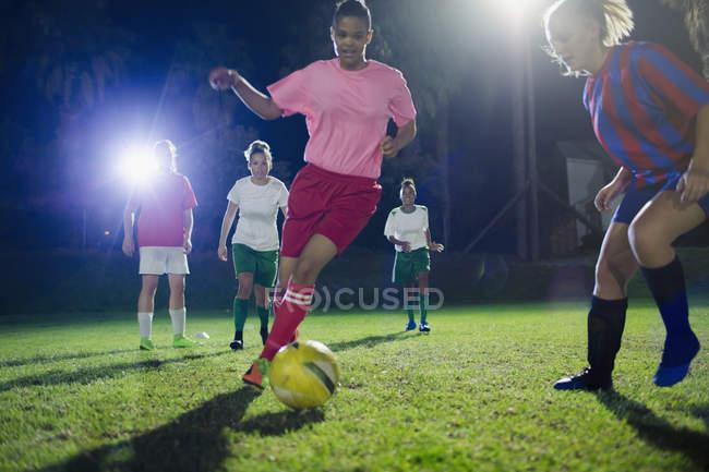 Жіночий футбол гравці, які грають на полі вночі, ногами м'яч — стокове фото