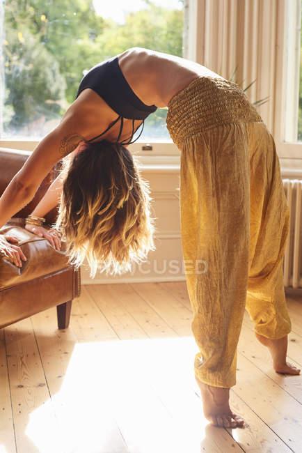 Flexible Frau praktizieren Yoga Backbend am sonnigen Fenster — Stockfoto