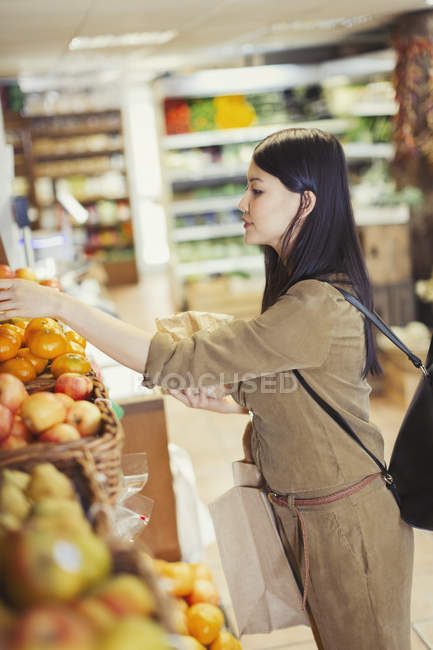 Young woman shopping for produce in grocery store — Stock Photo