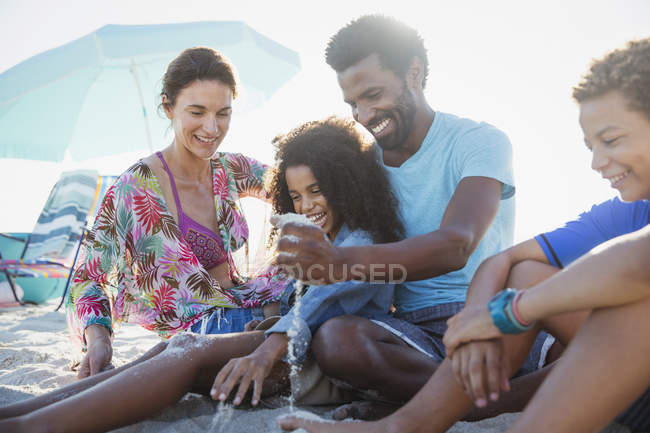 Family playing in sand on sunny summer beach — Stock Photo