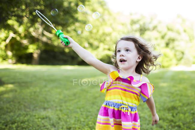 Fille préscolaire jouer avec baguette à bulles dans la cour d'été — Photo de stock