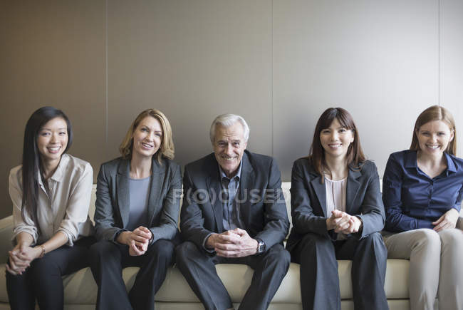 Portrait smiling business people in a row on sofa — Stock Photo