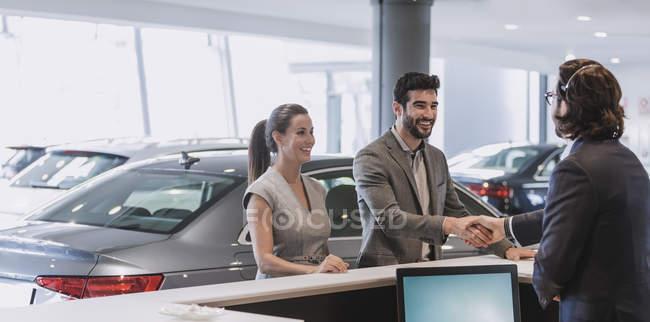 Coppia in arrivo, receptionist saluto e stretta di mano presso concessionaria auto showroom — Foto stock